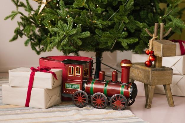 Regali di natale, locomotiva giocattolo e cervi di legno giocano sotto l'albero di natale