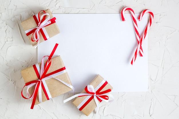 Regali e bastoncino di zucchero di natale con con la cartolina d'auguri in bianco