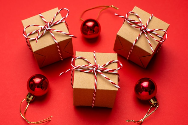 Regali e decorazioni natalizie su uno sfondo rosso colorato.