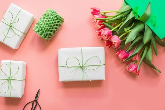 Regali e fiori rossi del tulipano in sacco di carta verde sul rosa. primavera. festa della mamma.