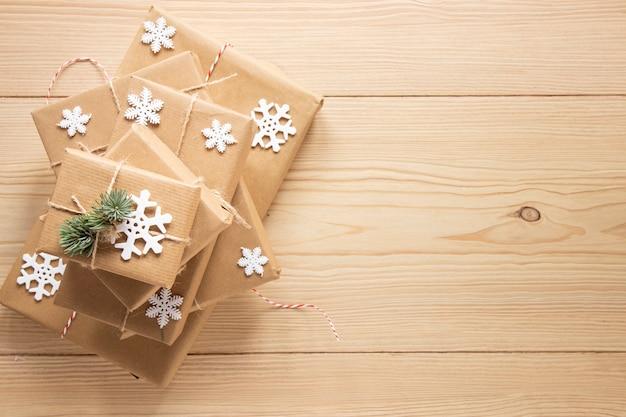 Regali festivi con fiocchi di neve su fondo di legno