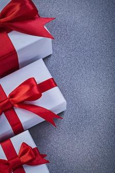 Regali in scatola con fiocchi rossi legati su superficie grigia