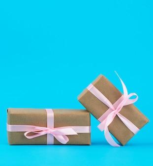 Regali in scatole avvolte in carta kraft marrone e legate con nastro di seta rosa