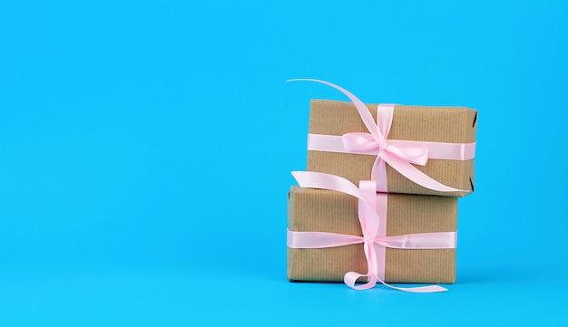 Regali in scatole avvolte in carta kraft marrone e legate con un nastro di seta rosa su un blu