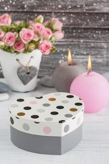 Regalo a forma di cuore, rose rosa in vaso di cemento con candela
