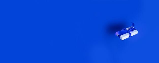 Regalo a sorpresa o scatola avvolta in carta e nastro di raso blu levitare in aria su un blu