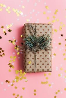 Regalo artigianale con spago e ramo di pino su pastello rosa con coriandoli dorati.