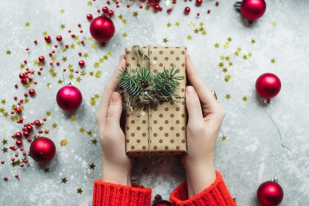 Regalo artigianale di carta marrone con ramoscelli di albero di natale e spago nelle mani di una ragazza in un maglione rosso
