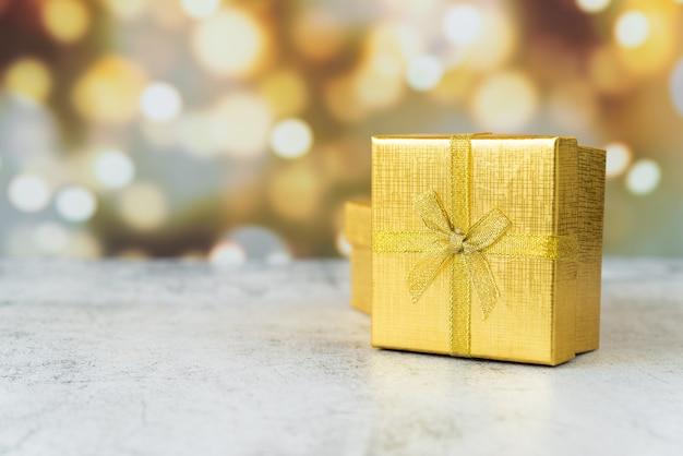 Regalo avvolto d'oro con effetto bokeh
