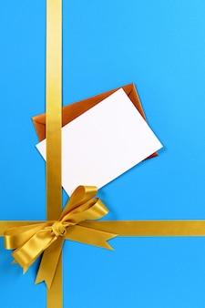 Regalo blu e oro con busta marrone metallizzato e biglietto di auguri o invito vuoto.