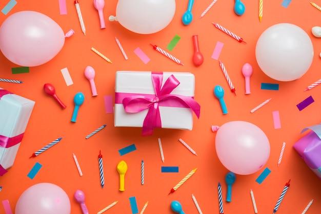 Regalo circondato da elementi di compleanno