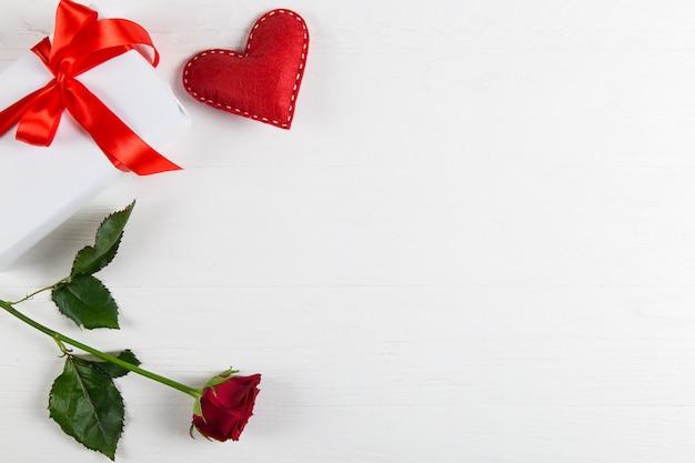 Regalo con nastro rosso, rosa rossa e cuore su bianco