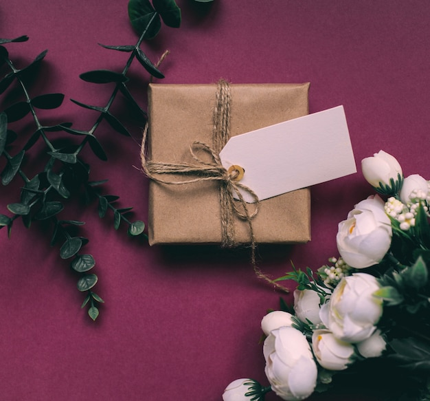 Regalo con un tag su uno sfondo luminoso rose bianche verdi e regalo su uno sfondo rosa regalo per la festa della donna e la festa della mamma
