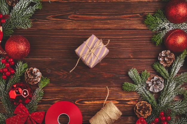 Regalo decorato alla moda di natale con il nastro su fondo di legno, vista superiore