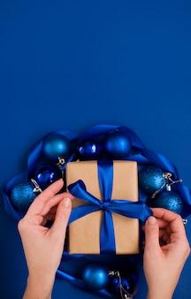 Regalo di capodanno su una superficie blu, con un bellissimo nastro di raso. natale. contenuto di capodanno