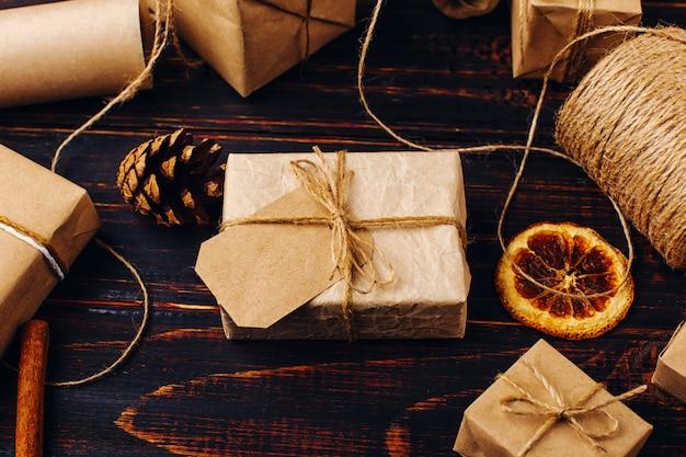 Regalo di carta artigianale sullo sfondo di arancia essiccata, cannella, pigne, anice su un tavolo di legno