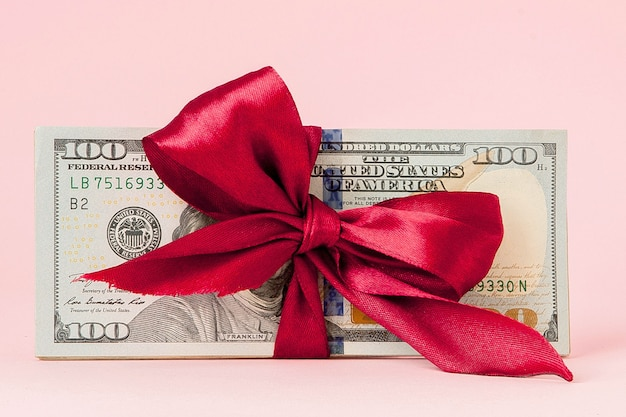 Regalo di cento dollari avvolto con un nastro rosso sul tavolo rosa