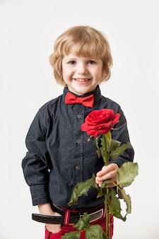 Regalo di festa fiori da un piccolo gentiluomo. rosa rossa nelle mani di un ragazzo su uno sfondo bianco