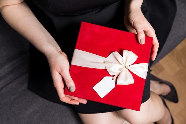 Regalo di giorno di biglietti di s. valentino con l'etichetta del regalo e primo piano dell'arco - tenuta della donna in mani presenti
