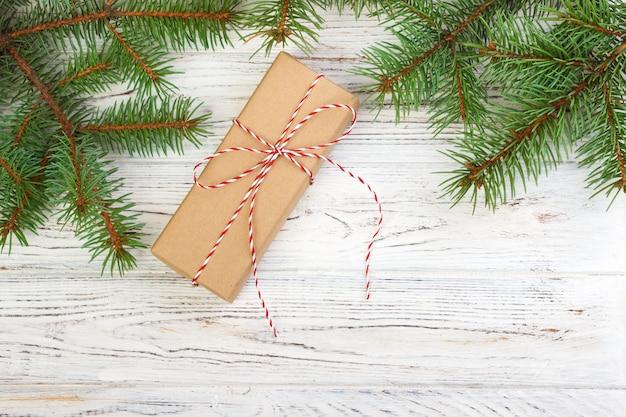 Regalo di natale con i bastoncini di zucchero su fondo di legno scuro nello stile d'annata