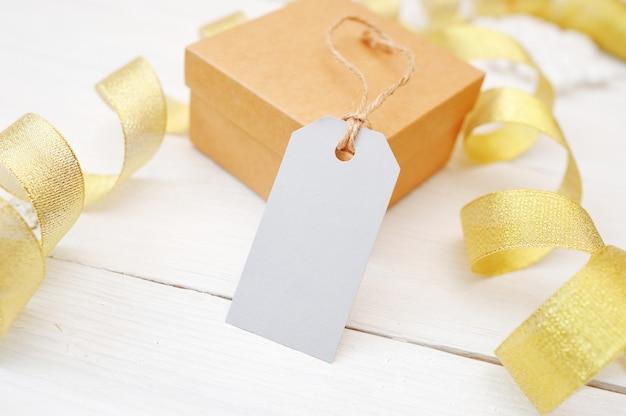 Regalo di natale del modello con l'etichetta in bianco su fondo di legno bianco