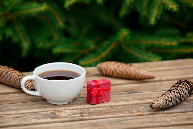 Regalo di natale e della tazza di caffè sulla tavola di legno con i rami attillati su fondo