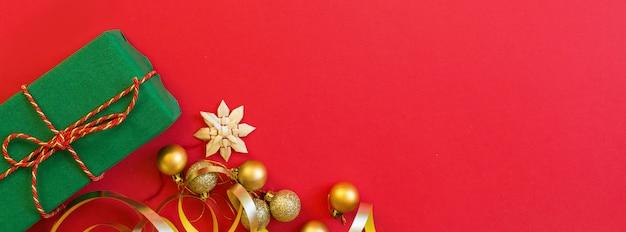 Regalo di natale, giocattoli dorati su colore rosso