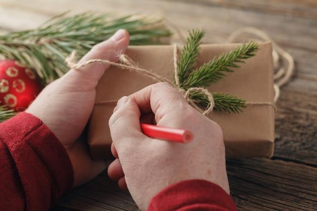 Regalo di natale. mani maschili tenendo presente di capodanno. regali e pergamene confezionati, luogo di lavoro per la preparazione di decorazioni fatte a mano.