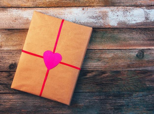 Regalo di san valentino in carta da imballaggio legata con il nastro rosso con cuore su legno retrò