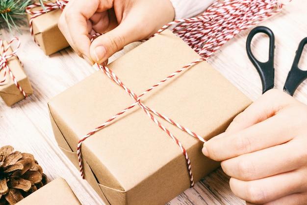 Regalo fatto a mano su legno con decorazioni natalizie. la donna che avvolge il regalo di natale, ragazza prepara i regali di natale con l'albero di abete e la pigna. vista dall'alto, copyspace. tonica