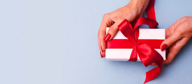 Regalo in mani femminili su uno sfondo blu. scatola bianca con un nastro rosso e una manicure rossa. banner per san valentino, natale o compleanno