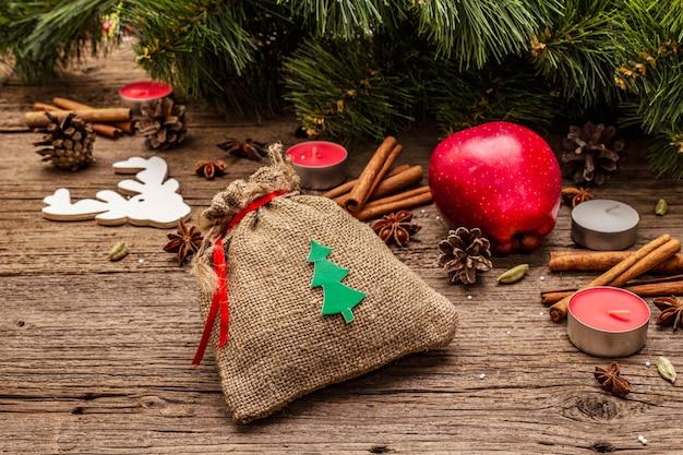 Regalo in sacco, albero di capodanno, mela, candele, spezie, cervi, coni. decorazioni naturali, tavole di legno vintage