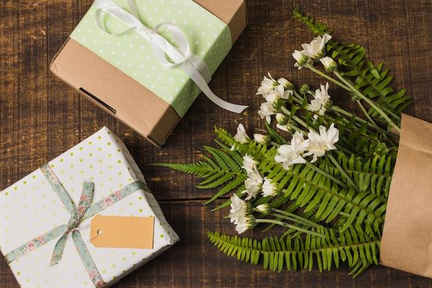Regalo in scatola con fiori e foglie in sacchetto di carta sul tavolo di legno