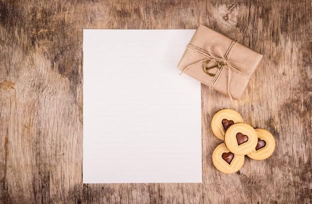 Regalo per san valentino, foglio di carta vuoto, confezione regalo e cuori di cioccolato