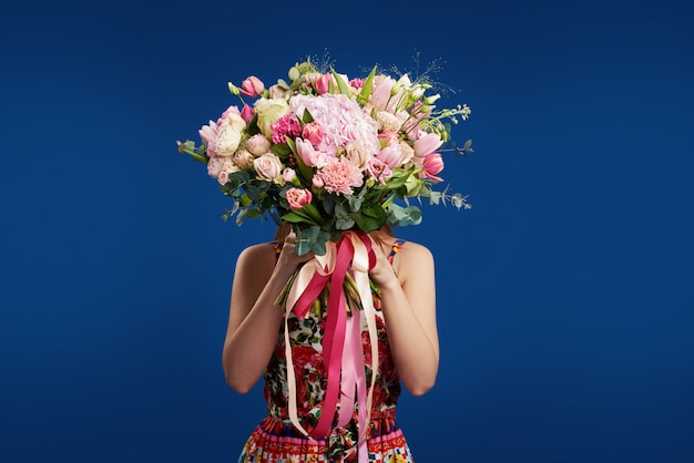 Regalo perfetto fiori meravigliosi per la festa della donna. tenera donna sorridente della brunetta che tiene davanti al fronte il mazzo del fiore della molla spazio per testo