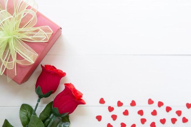 Regalo presente con fiore rosa rossa e confezione regalo con fiocco nastro e cuore sulla tavola di legno