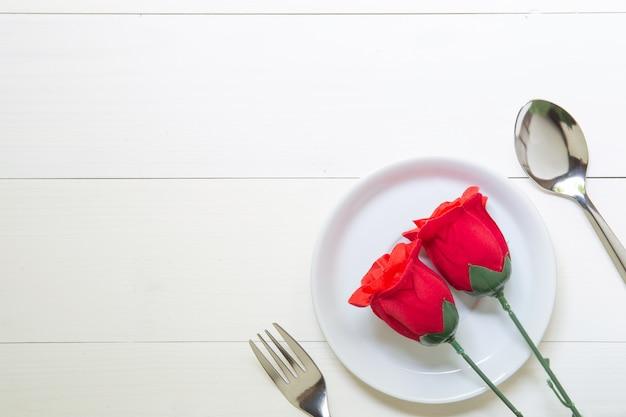Regalo presente con fiore rosa rossa e piatto e cucchiaio e forchetta sul tavolo di legno