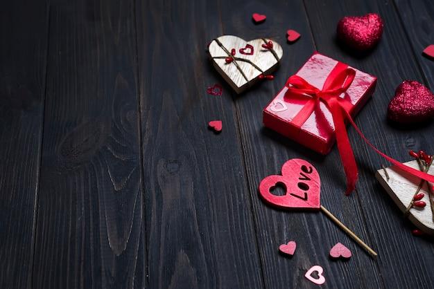 Regalo rosso delle feste e cuore su fondo di legno