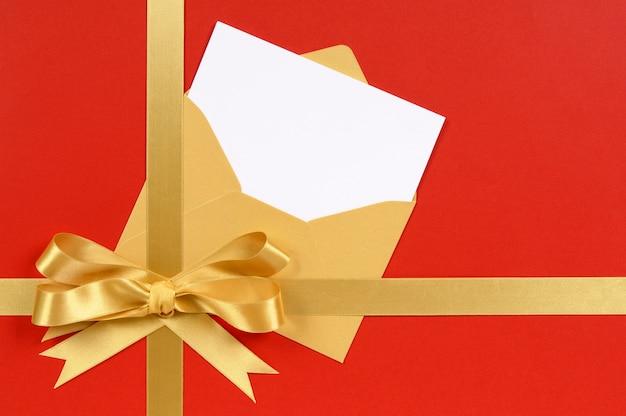 Regalo rosso e oro con invito in bianco o biglietto di auguri.