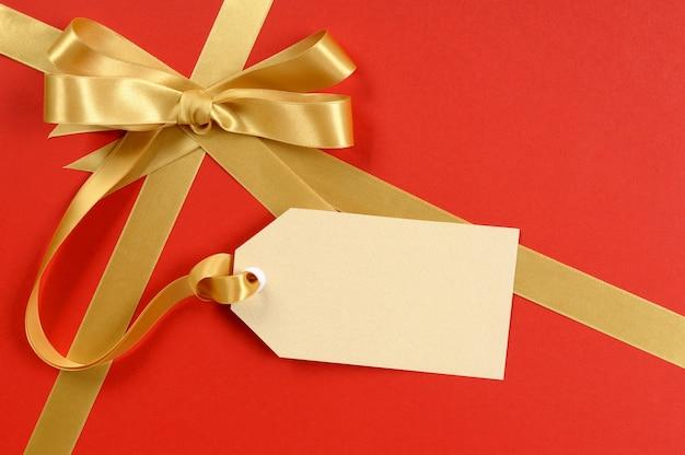 Regalo rosso, fiocco in nastro d'oro, etichetta regalo vuota o etichetta, copia spazio