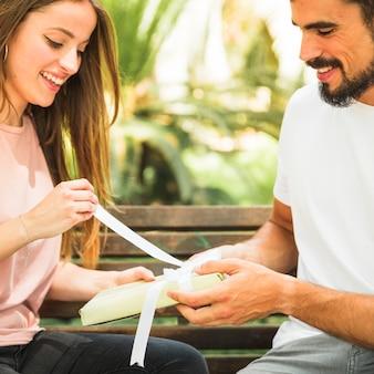 Regalo unwrapping sorridente della giovane donna comprato dal suo ragazzo