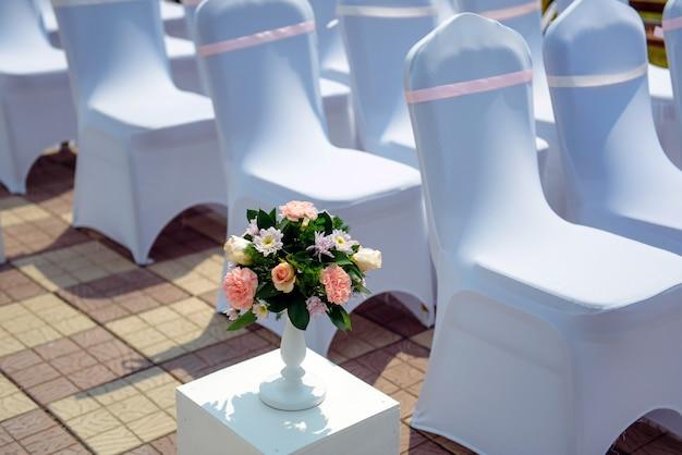 Registrazione di uscita degli sposi, cerimonia di matrimonio a cielo aperto, file di sedie con mantelle bianche