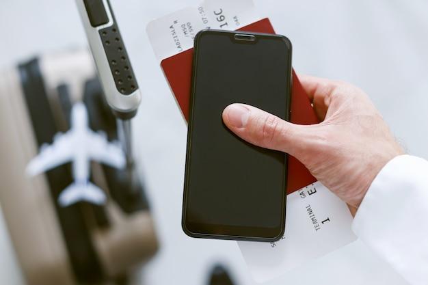 Registrazione elettronica tramite smartphone per salire a bordo dell'aereo. l'uomo con una valigia tiene un biglietto telefonico e un passaporto.