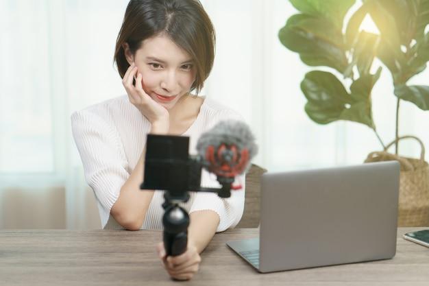 Registrazione femminile di blogger che trasmette video a casa, modo, trucco, concetto di tecnologia