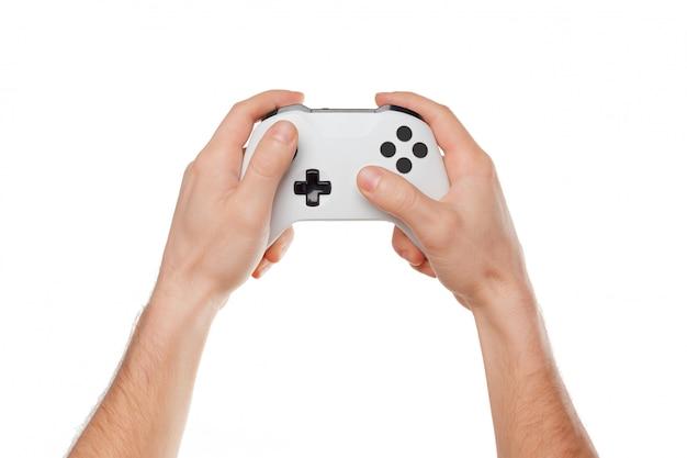 Regolatore della console del videogioco in mani del giocatore isolate