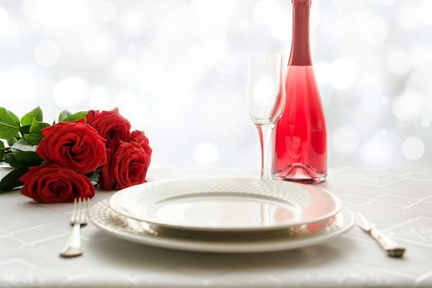 Regolazione del posto di giorno di san valentino con rose rosse e champagne. invito per una data.