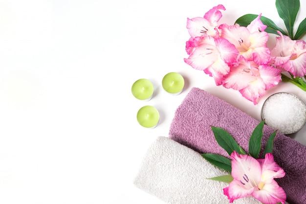 Regolazione della stazione termale dell'asciugamano, fiore isolato su bianco con lo spazio della copia.