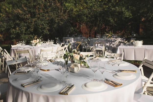 Regolazione della tabella di banchetti di nozze decorata con fiori freschi in un vaso di ottone