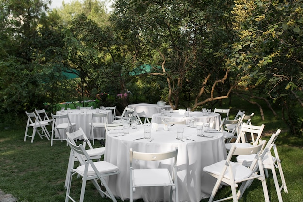 Regolazione della tabella di cerimonia nuziale decorata con i fiori freschi in un vaso d'ottone. floristica per matrimoni. tavolo per banchetti all'aperto per gli ospiti con vista sul verde. bouquet di rose, foglie di eustoma ed eucalipto.