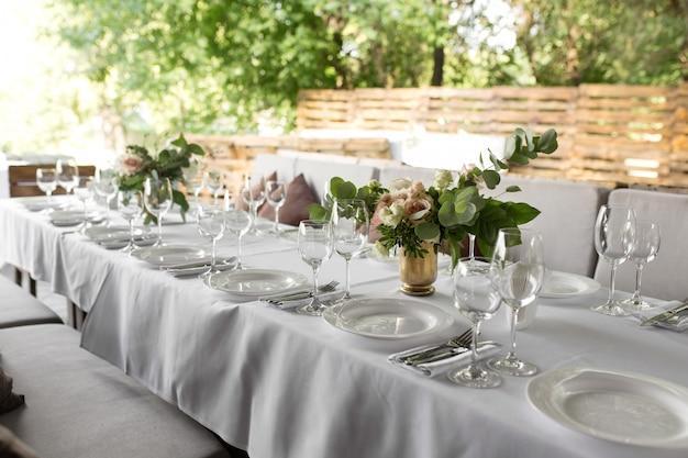 Regolazione della tabella di cerimonia nuziale decorata con i fiori freschi in un vaso d'ottone